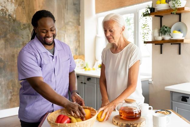 Социальный работник делает еду с пожилой женщиной