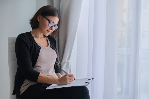 Social worker, psychologist sitting near window with clipping board