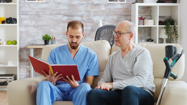 Social worker reading a book to an old disabled man in nursing home.