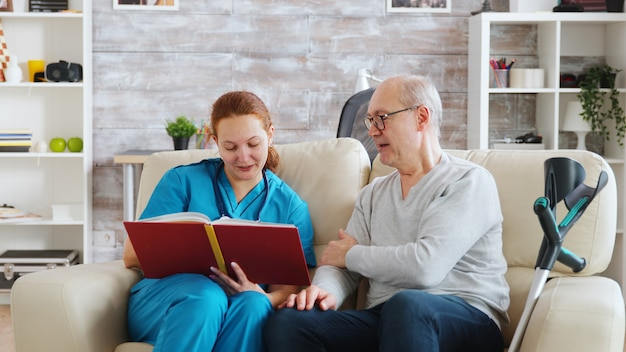 Social worker reading to an old and disabled man sitting on a sofa in bright nursing home