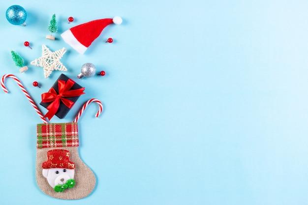 Носок и рождественские украшения на пастельно-синем фоне. красивая рождественская открытка с копией пространства.