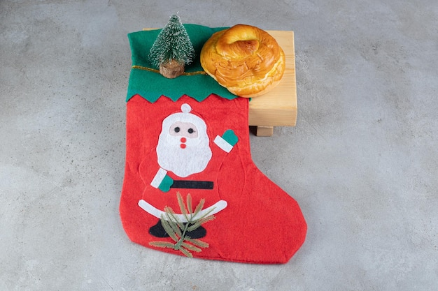 Sock with santa illustration, sweet bun and a small tree figurine on marble table.