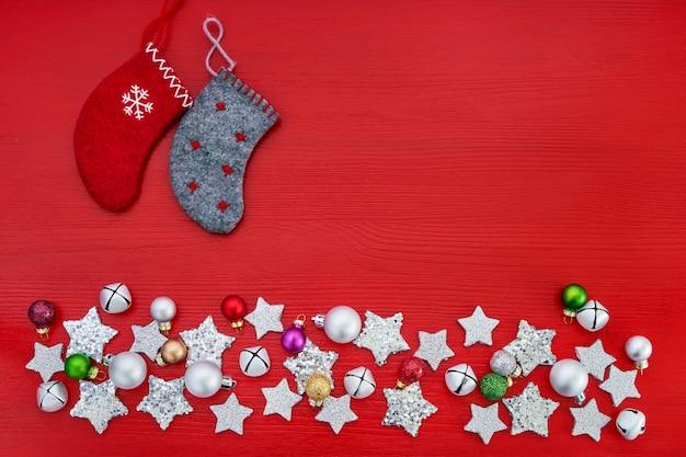 クリスマスのグリーティングカード。赤の背景に赤のクリスマスsockaとクリスマスの装飾。トップビュー、copyspace。