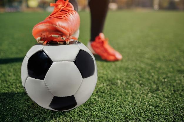 Закройте ноги футболиста в кроссовки socker. он держит это на мяче. мяч стоять на зеленой лужайке.