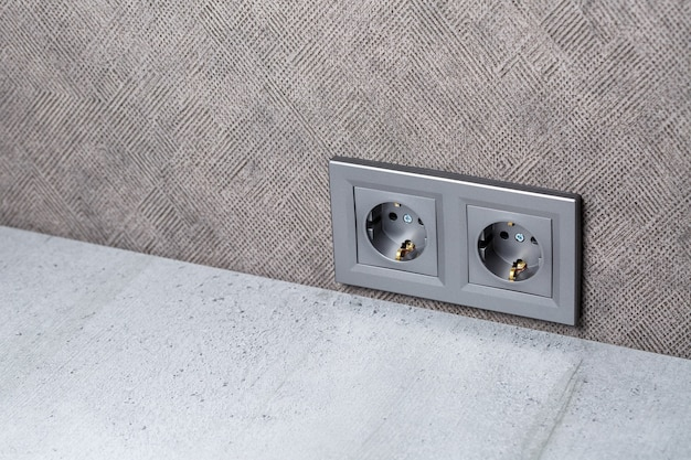2つのデバイス用の入力を備えたアース付きのソケットグレー。彼女はカウントテーブルの上の灰色の壁にいます。電気と修理のコンセプト