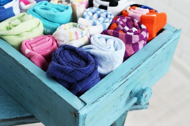 Носки в цветной ящик на фоне белой кирпичной стены