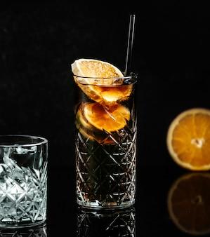 Сода в черном стакане с ломтиком лимона