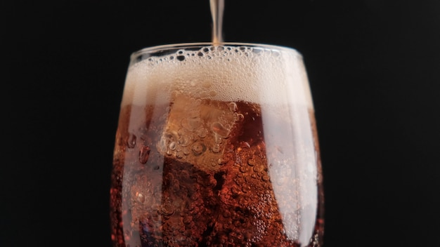 Soda with ice on a black background close-up