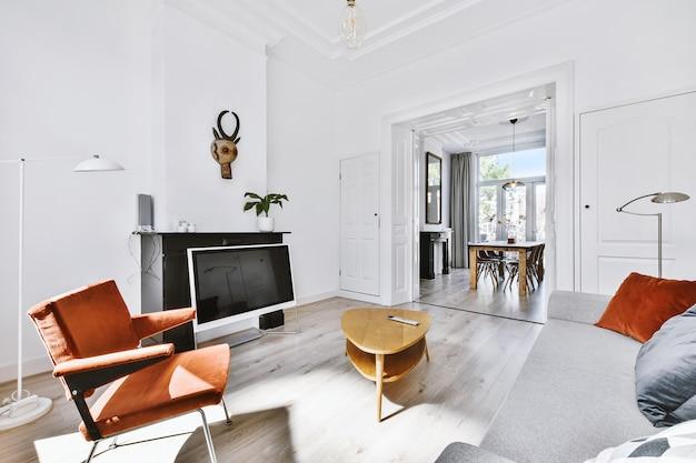現代的な家のダイニングルームへのアーチの近くのテーブルの近くにあるソファとアームチェア