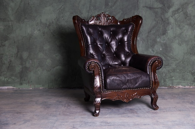 Sofa of brown leather standing in center on concrete floor against dark grey wall with copy space. vintage brown leather sofa with grunge gray wall living room.
