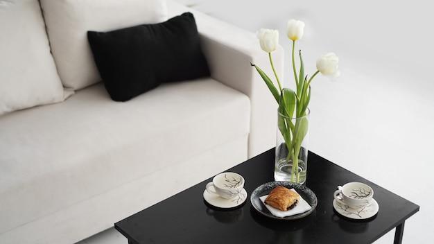 현대적인 인테리어의 소파입니다. 테이블에는 튤립 꽃다발, 커피 컵, 달콤한 롤빵이 있습니다. 흑백 인테리어와 햇살 가득한 분위기.