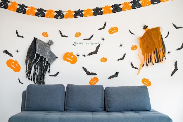 장면이 있는 방의 소파는 할로윈으로 설정됩니다. 매달려 있는 장식품, 할로윈 축제의 장면들이 방의 벽에 걸려 있습니다. 할로윈 장식의 장식입니다.