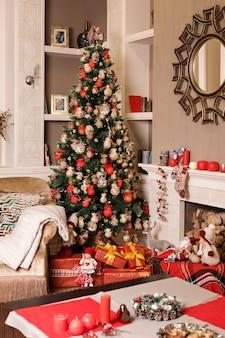 装飾されたクリスマスツリーの近くのソファと薪の暖炉