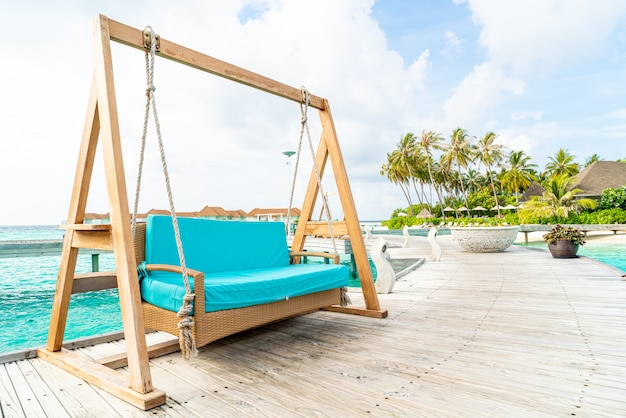 Sofa swing with tropical maldives resort and sea background