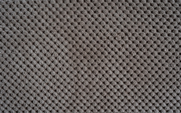Sofa upholstery closeup texture of rough dense ribbed fabric beige background