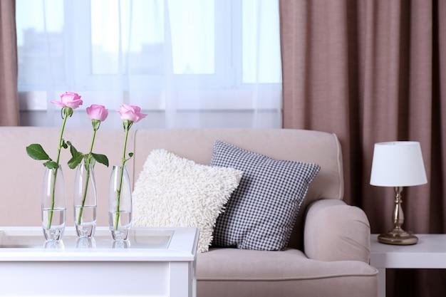 Диван с красивыми подушками и сфокусированной вазой с цветами на столе перед ним в комнате