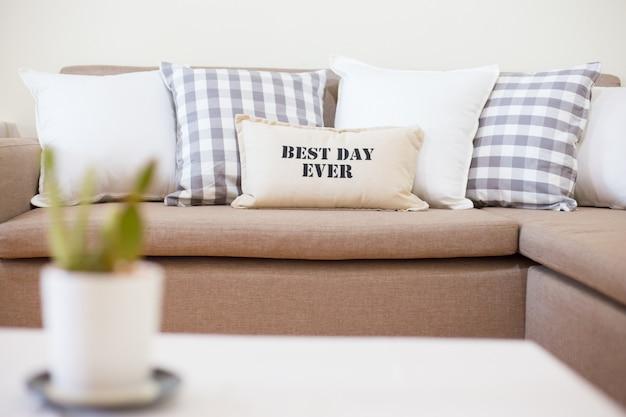 リビングルームに多くのモダンな枕が付いているソファー