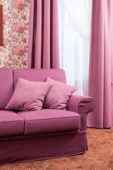 窓の近くのソファーに2つの枕が付いているソファー