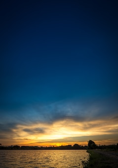 日没時の川沿いの青い空に柔らかくモーションブラー雲