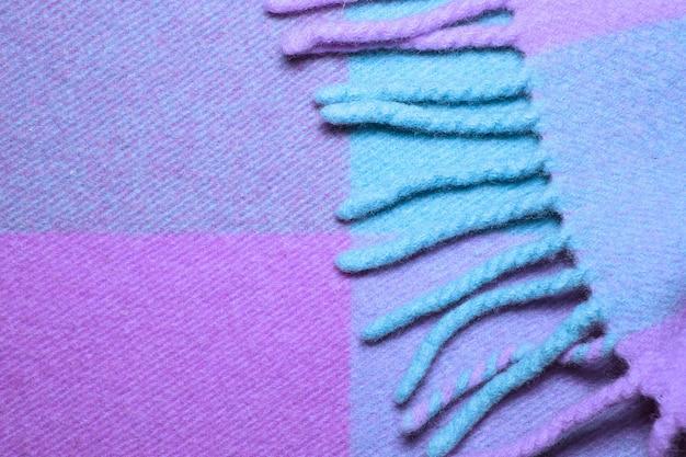Мягкое и теплое сложенное одеяло из шерсти альпаки с бахромой. синий и фиолетовый шерстяной плед текстуры макросъемки. шерстяная клетчатая текстура с бахромой. одеяло из шерсти