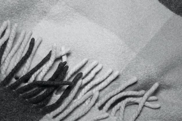 Мягкое и теплое сложенное одеяло из шерсти альпаки с бахромой. съемка макроса текстуры шотландки серой шерсти. шерстяная клетчатая текстура с бахромой. одеяло из шерсти