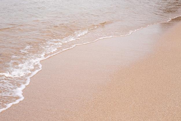 Мягкая красивая морская волна на песчаном пляже. фоновая текстура. мокрый песчаный пляж