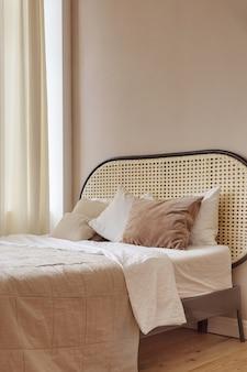 Мягкая кровать с подушками и одеялом расположена в уютной спальне в современной квартире