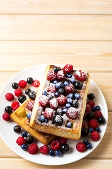 Soft belgian waffles with blueberry, raspberry, blackcurrant and caster sugar copy space