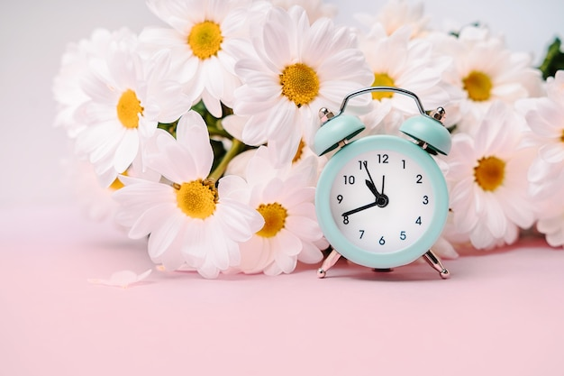 A soft blue alarm clock in a bouquet of daisies. floral concept for holidays