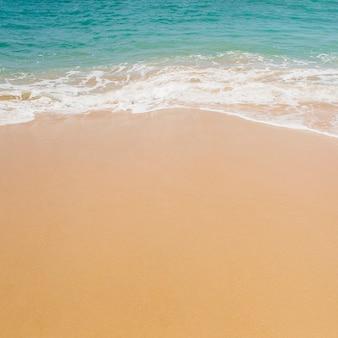 Soft blue ocean wave on sandy beach.