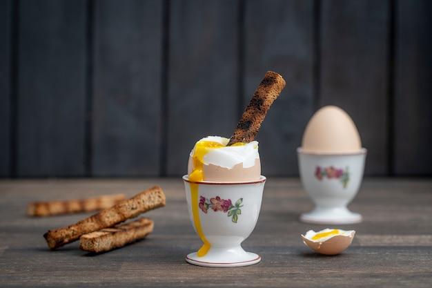 木製のテーブルの上の卵カップで半熟卵とトーストパン。閉じる。健康的な朝食