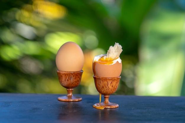 Вареное яйцо всмятку в яичной чашке с ломтиком поджаренного хлеба на деревянном столе на фоне природы, крупным планом