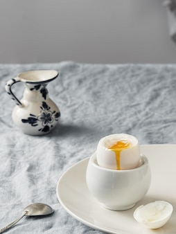 Soft-boiled egg, light breakfast. white ceramic plate with soft-boiled egg, on a white ceramic plate, on a blue tablecloth.