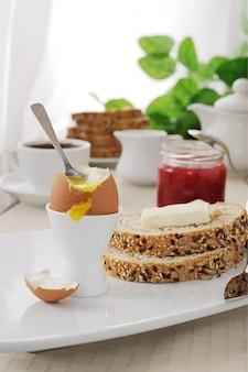 아침으로 버터와 함께 오트밀 빵 조각을 곁들인 반숙 계란