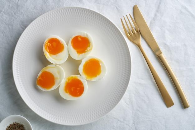 半熟卵、皮をむいて半分に切り、白い皿の上に置く