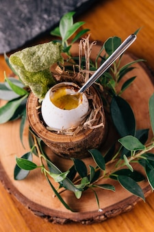 Soft-boiled eggs with shell decorated with small branches, leaves and straw.