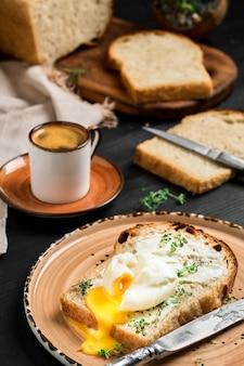 黒い木製のテーブルの粘土板に、バタークリームとハーブで覆われたパンのスライスにソフトボイルド(ポーチド)エッグ。ぼやけた壁にエスプレッソコーヒーとスライスされたパンの塊。朝食のアイデア