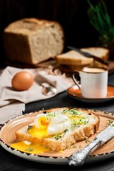 黒い木製のテーブルの粘土板の上に、バタークリームとハーブで覆われたパンのスライスにソフトボイルド(ポーチド)エッグ