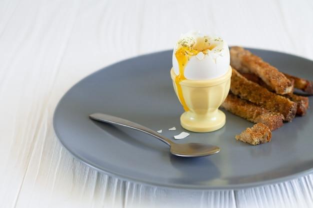 朝食にトーストしたパンを入れた卵カップの半熟半熟卵