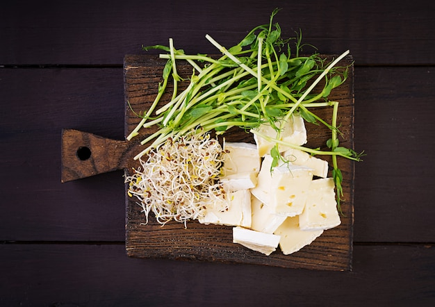 Soft brie cheese and microgreens on wooden board