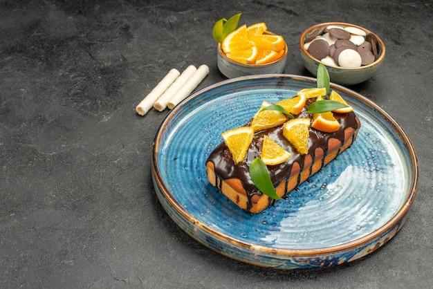 トレイと他のクッキーの暗いテーブルにオレンジとチョコレートで飾られた柔らかいケーキ