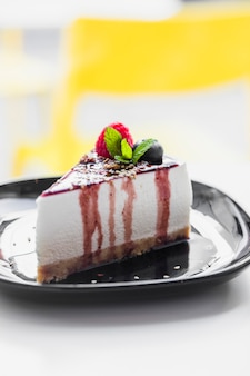 Soft cake topped with raspberry; mint; blueberry & chocolate sauce served on black plate against blur backdrop