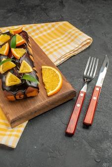 ボード上の柔らかいケーキと暗いテーブル映像の緑の剥ぎ取られたタオルの上の葉でレモンをカット
