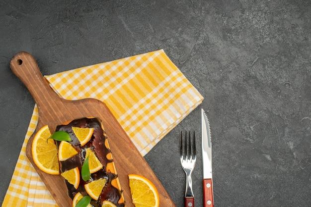 ボード上の柔らかいケーキと暗いテーブルの緑の剥ぎ取られたタオルの上の葉でレモンを切る