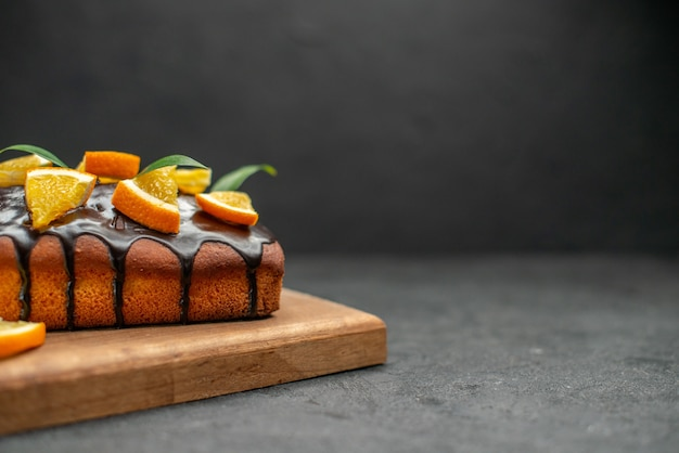 커팅 보드에 부드러운 케이크와 어두운 테이블에 잎을 가진 오렌지를 잘라