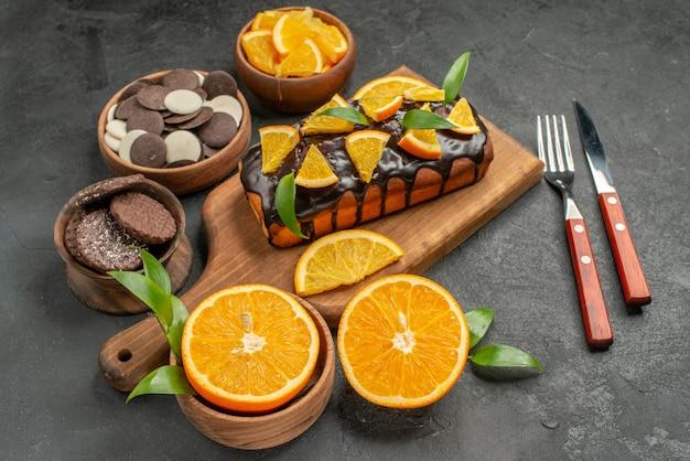 나무 커팅 보드에 부드러운 케이크와 어두운 테이블 측면보기에 잎 비스킷으로 오렌지를 잘라