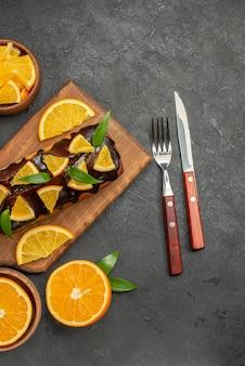 나무 커팅 보드에 부드러운 케이크와 어두운 테이블에 잎 비스킷으로 오렌지를 잘라