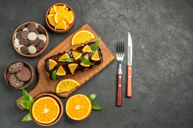 Soft cakes on wooden cutting board and cut oranges with leaves biscuits on dark table