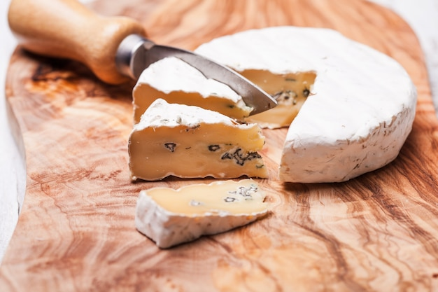 Мягкий сыр с прожилками голубой плесени и твердой белой кожицей. два вида плесени в сырном дуэте
