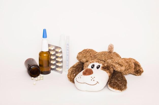 옆에 약과 정제가 있는 부드러운 어린이 장난감 개. 어린이의 건강과 질병, 바이러스로부터 어린이 보호의 개념.